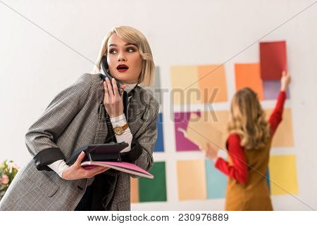 Magazine Editor Talking On Phone While Her Colleague Working With Color Palette Behind