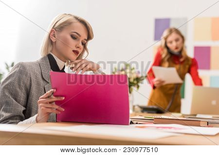 Fashion Magazine Editor Doing Paperwork In Modern Office With Colleague Colleagues