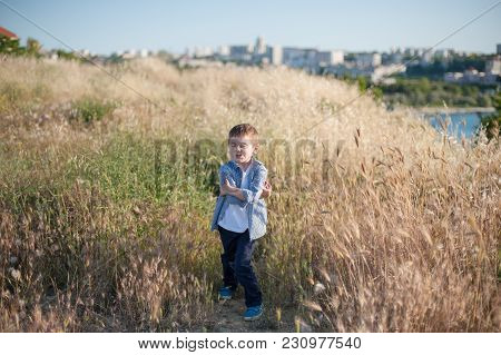 Funny Cute Little Boy Grimacing Standing In The Middle Of A Field Of Plants