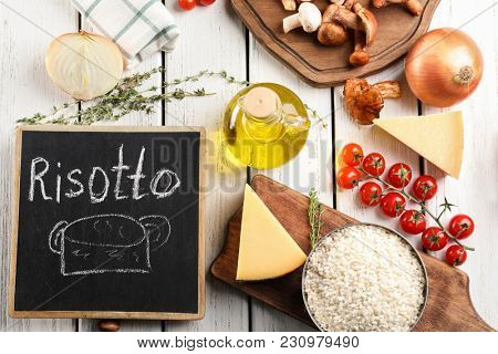 Composition with ingredients for risotto on wooden background