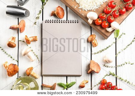 Notebook and ingredients for risotto with mushrooms on wooden background