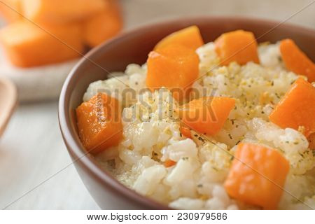 Dish with delicious pumpkin risotto on table