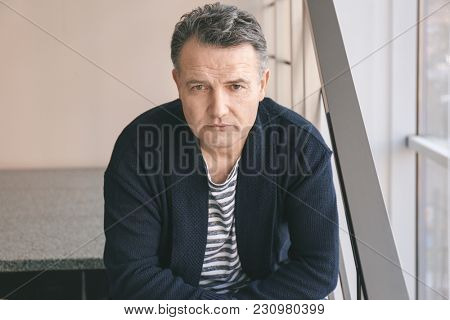 Portrait of serious male pensioner at home