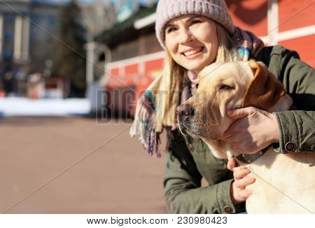 Woman with her cute lovely dog outdoors. Friendship between pet and owner