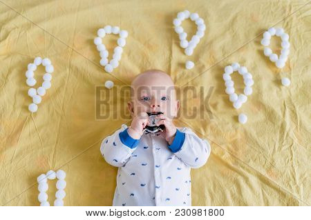 Top View Of Infant Child Surrounded With Exclamation Marks Made Of Cotton Balls Biting Alarm Clock I