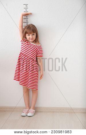 Cute little girl measuring height near light wall