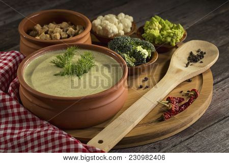 High Angle View Of Fresh Creamy Broccoli Soup With Some Fresh Vegetables, Spices And Croutons Next T