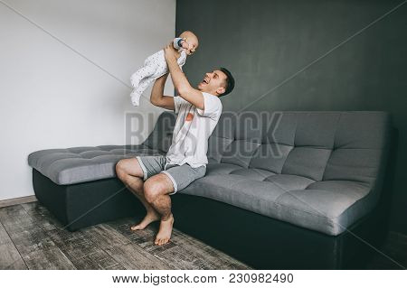 Happy Young Father Sitting On Sofa And Playing With Adorable Infant Child
