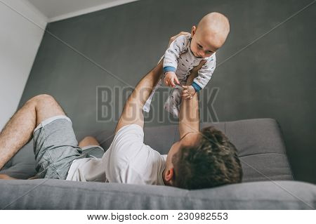 Young Father Lying On Sofa And Playing With Cute Infant Child