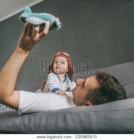 Father Holding Toy Plane While Lying On Sofa And Playing With Infant Child In Knitted Pilot Hat