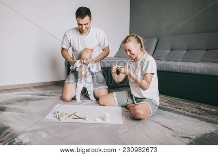 Happy Young Family With Little Infant Child Painting Together On Floor At Home