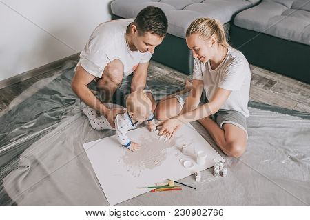 High Angle View Of Happy Young Family With Beautiful Little Infant Child Painting Together On Floor