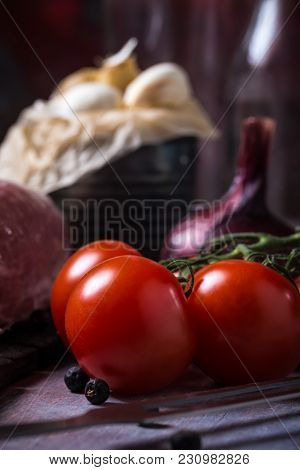 Detail Of Red Cherry Tomatoes Next To Pork Tenderloin On Wooden Board