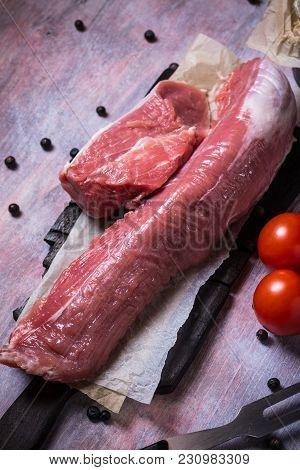 Whole Pork Tenderloin Meat On Vintage Wooden Board