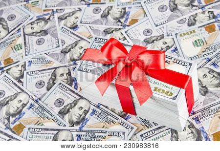 Gift  With Big Red Bow Ribbon Made Of United States Dollars Currency Bundle On Many New One Hundred