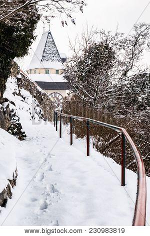 Path To Snow Covered Uhrturm Clocktower Landmark Of City Graz On Hill Schlossberg In Winter