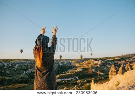 A Tourist Girl In A Hat Admires Hot Air Balloons Flying In The Sky Over Cappadocia In Turkey. Impres