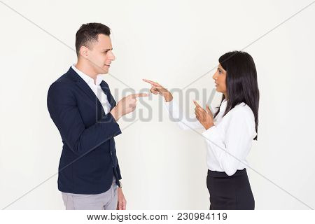 Portrait of displeased young multiethnic colleagues, Indian woman and North American man, accusing each other pointing fingers. Guilt and business relationships problems concept poster