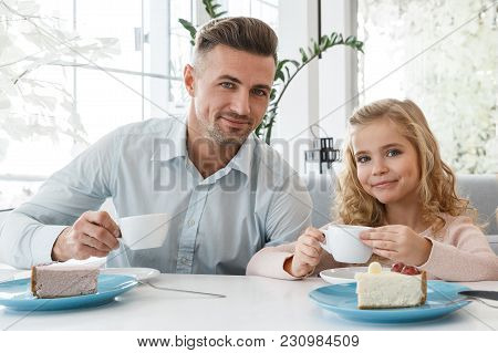 Handsome Father And Young Daughter Spending Time Together At Cafe