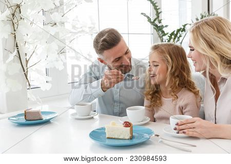 Father Feeding His Daughter With Cake While They Spending Time In Cafe Together