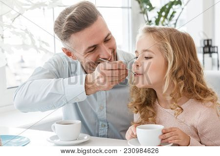 Happy Young Father Feeding His Daughter At Cafe