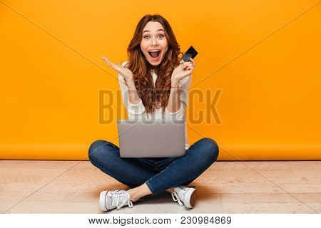 Surprised happy brunette woman in sweater sitting on the floor with laptop computer while holding credit card and looking at the camera over yellow background