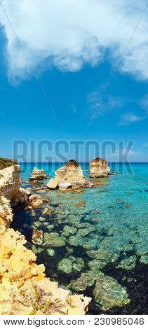 Picturesque Seascape With White Rocky Cliffs, Sea Bay, Islets And Faraglioni At Beach Spiaggia Della