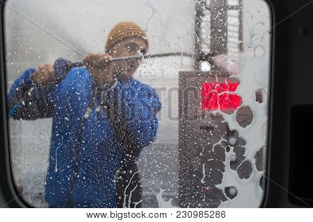 A Man Washes A Car From A Hose Behind The Car Window