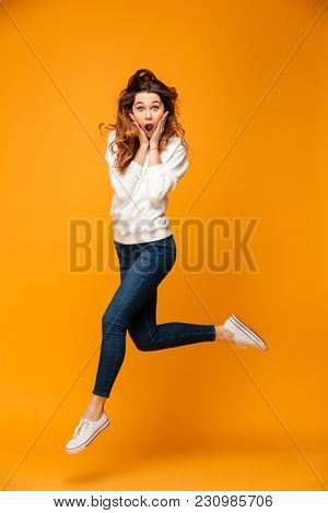 Full length image of Shocked brunette woman in sweater jumping while holding her cheek and looking at the camera over yellow background