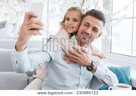 Daughter Kissing Her Father While They Taking Selfie