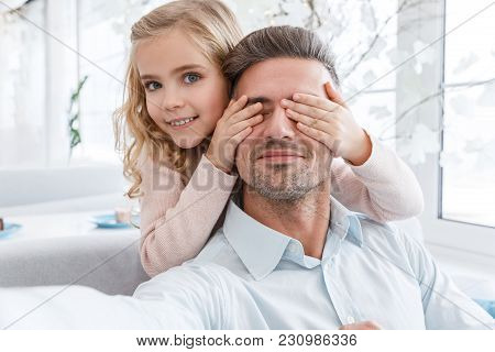 Daughter Covering Eyes Of Father While They Taking Selfie