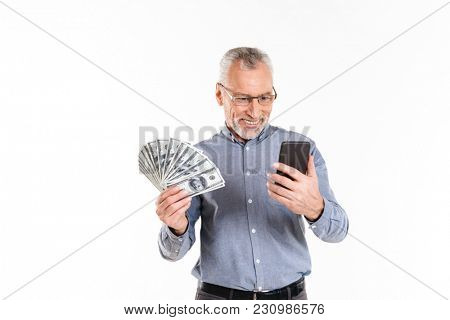 Cheerful grey-haired mature man holding dollars and using smartphone isolated over white