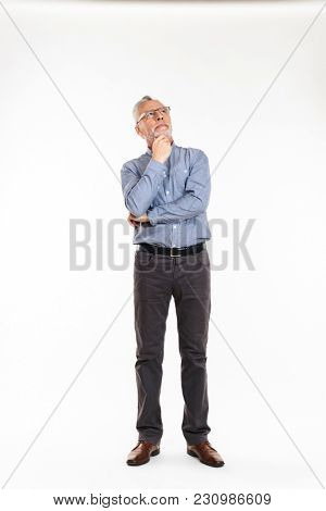 Pensive mature man in eyeglasses and formal wear looking up and thinking isolated over white