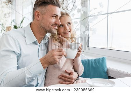 Young Father And Daughter Drinking Tea In Cafe Together