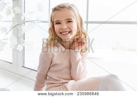 View Of Happy Little Child Sitting On Windowsill