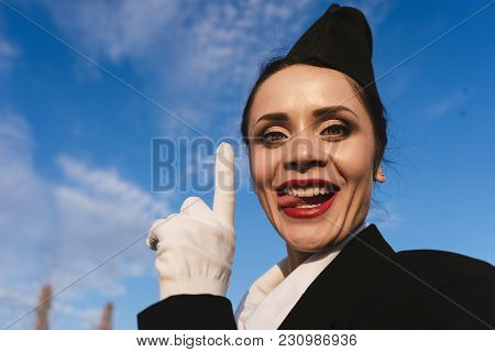 Funny Beautiful Young Woman Stewardess In Uniform Shows Tongue, Against Blue Sky Background