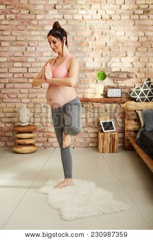 Pregnant woman doing yoga exercise at home standing.