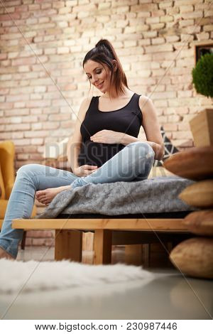 Happy pregnant woman sitting on bed at home smiling, relaxing.