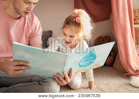 Father and his daughter reading book on floor in children room