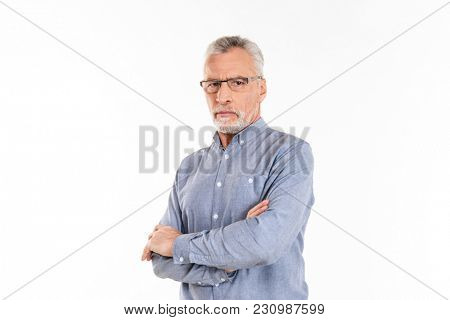 Portrait of serious confident mature man in eyeglasses looking camera with folded hands isolated