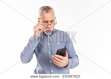 Shocked mature man in eyeglasses looking at smartphone isolated over white