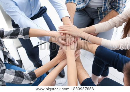 People putting their hands together at group therapy session