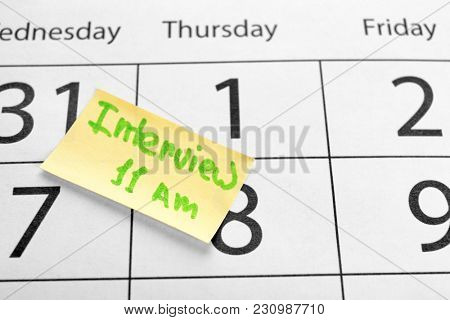 Sticky note with reminder about job interview on calendar page, closeup