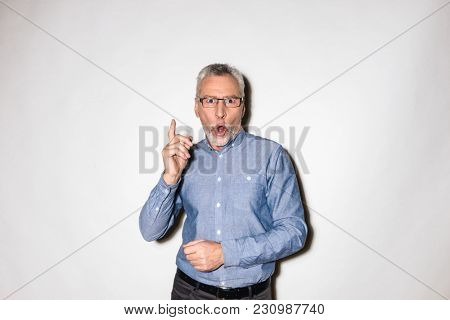 Surprised mature man looking camera with opened mouth and pointing up with finger isolated over white