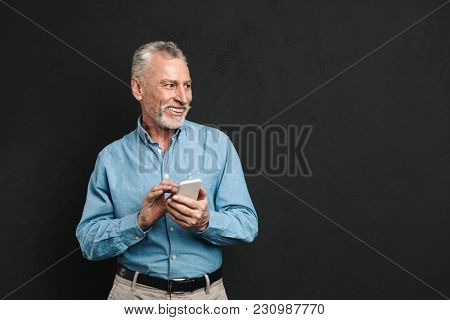 Image of bearded male pensioner 60s with gray hair chatting or browsing internet on mobile phone isolated over black background