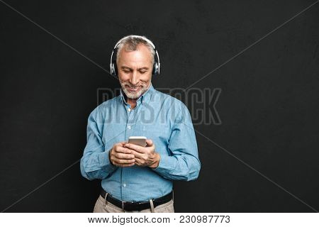 Portrait of unshaved male pensioner 60s with gray hair listening to music via wireless earphones using mobile phone isolated over black background