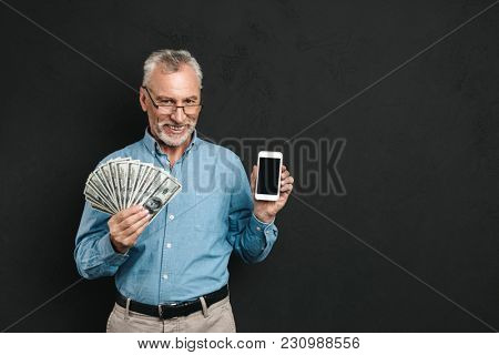 Photo of caucasian retired man 60s with gray hair holding mobile phone and lots of money dollar currency isolated over black background
