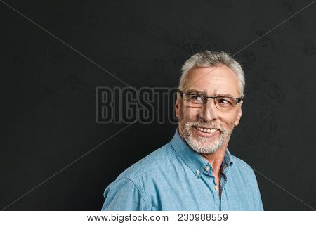 Horizontal portrait of mature unshaved man 60s with grey hair wearing eyeglasses smiling and looking aside on copyspace isolated over black background