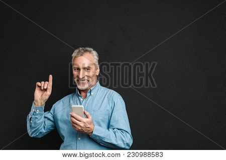 Image of bearded male pensioner 60s with gray hair pointing finger upward like have idea while using mobile phone isolated over black background