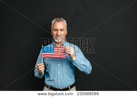 Portrait of caucasian male pensioner 60s with gray hair and beard in shirt holding small american flag with proud and smiling isolated over black background